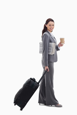 Profile of a businesswoman smiling with a suitcase, a newspaper and a coffee against white background Stock Photo - 13600615
