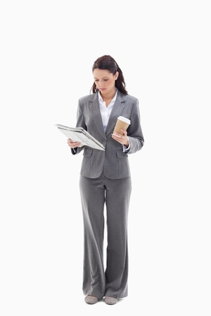 Businesswoman with a coffee reading a newspaper against white background photo