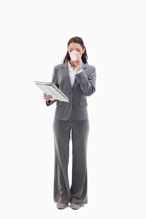 19's: Businesswoman drinking a coffee and reading a newspaper against white background Stock Photo