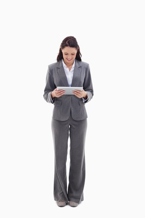 Businesswoman smiling watching a touch pad against white background photo