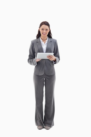 Businesswoman smiling with a touch pad against white background photo