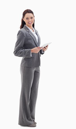 Profile of a businesswoman smiling with a touch pad against white background photo