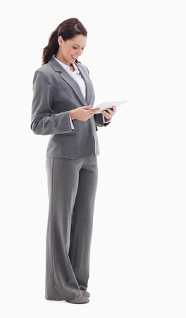 Profile of a businesswoman smiling while watching a touch pad against white bacground photo