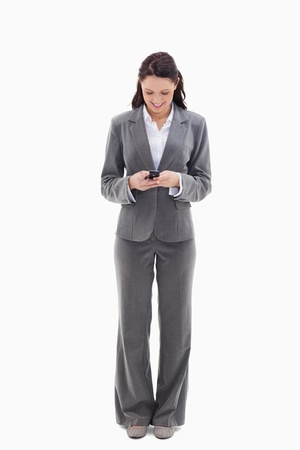 19's: Businesswoman writing a text message against white background