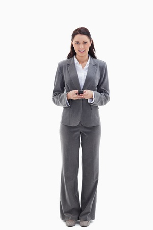 pantsuit: Businesswoman smiling while holding her mobile against white background
