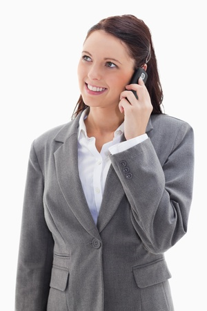 19's: Businesswoman looking up while smiling on the phone against white background