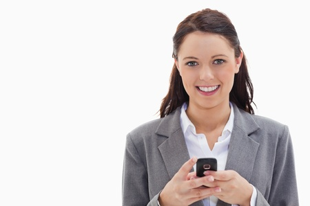 Close-up of a businesswoman smiling and holding her mobile against white background photo
