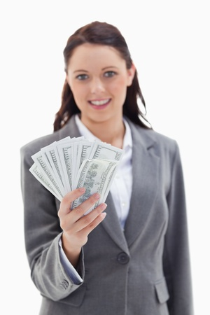 19's: Close-up of a businesswoman smiling and holding a lot of dollar bank notes with focus on bank notes against white background