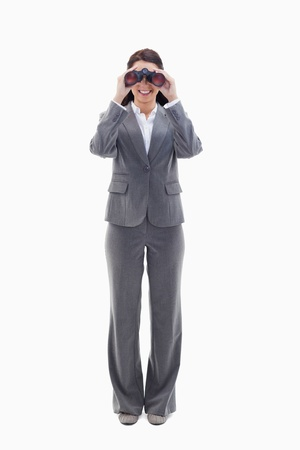 19's: Businesswoman smiling and looking through binoculars against white background
