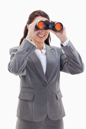 19's: Close-up of a businesswoman smiling and looking through binoculars on the left side against white background Stock Photo