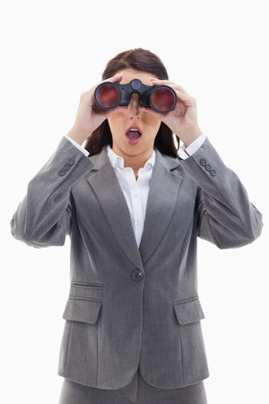 Close-up of a surprised businesswoman looking through binoculars against white background photo