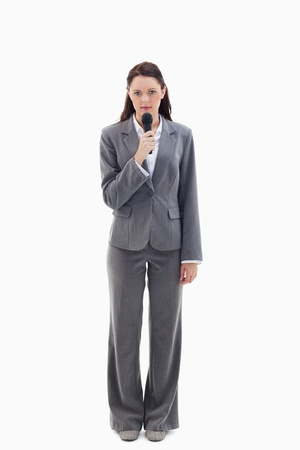 Serious businesswoman holding a microphone against white background