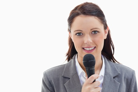 Close-up of a businesswoman holding a microphone against white background photo