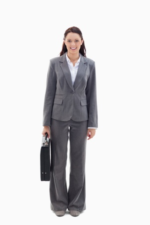 19's: Businesswoman smiling with briefcase against white background Stock Photo