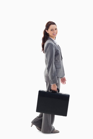 Profile of a business woman smiling and walking with a briefcase against white background photo