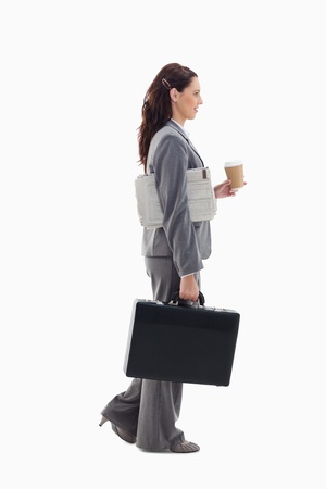 19's: Profile of a businesswoman walking with a briefcase, with a newspaper under her arm and holding a coffee against white background Stock Photo