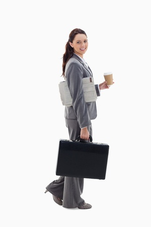 19's: Profile of a businesswoman smiling, walking with a briefcase, with a newspaper under her arm and holding coffee against white background