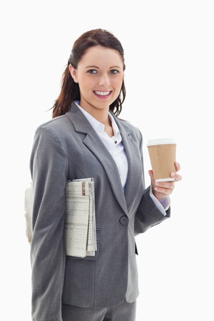 Close-up profile of a businesswoman smiling with a newspaper under her arm and holding a coffee against white background photo