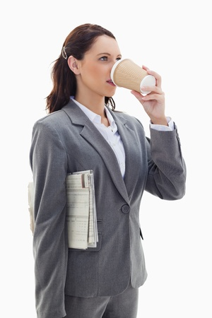 Close-up of a profile businesswoman with a newspaper and drinking a coffee against white background photo