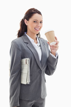 19's: Close-up of a profile businesswoman smiling with a newspaper and drinking a coffee against white background Stock Photo