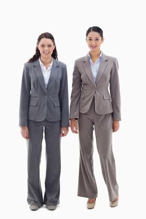 19's: Two businesswomen smiling against white background