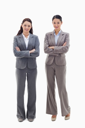 Two businesswomen smiling and crossing their arms against white background Stock Photo - 13609420