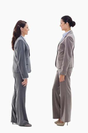 19's: Two businesswomen smiling face to face against white background