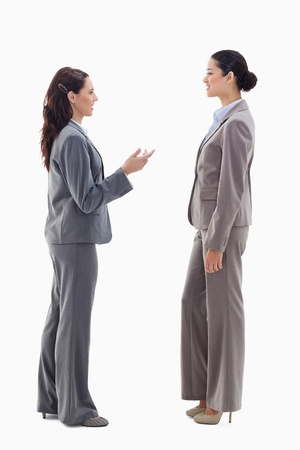 19's: Two businesswomen talking face to face against white background