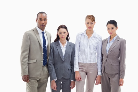 Serious business team side by side against white background photo