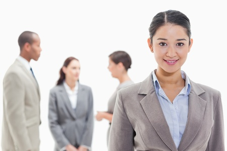19's: Close-up of a businesswoman smiling with co-workers in the background Stock Photo