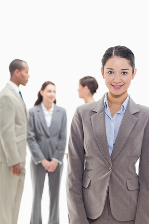 19's: Businesswoman smiling with co-workers talking in the background against white background