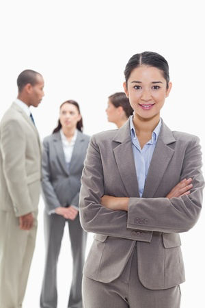 19's: Businesswoman smiling and crossing her arms with co-workers talking in the background Stock Photo