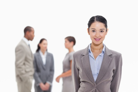 19's: Close-up of a businesswoman smiling with co-workers talking in the background
