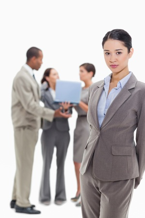19's: Serious businesswoman with co-workers talking with a laptop in the background Stock Photo