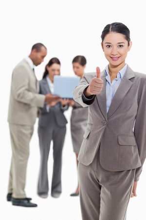 19's: Businesswoman smiling and approving with co-workers watching a laptop in the background Stock Photo