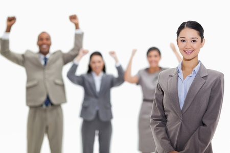 Close-up of a businesswoman smiling with enthusiastic co-workers raising their arms in the background photo