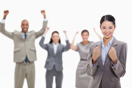 Close-up of a businesswoman smiling and clenching her fists with enthusiastic co-workers in the background Stock Photo - 13608912