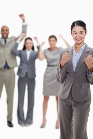 Close-up of a happy businesswoman clenching her fists with enthusiastic co-workers in the background Stock Photo - 13616085