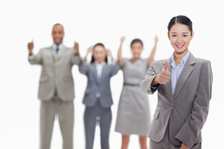 four fingers: Happy businesswoman approving with her co-workers in the background Stock Photo