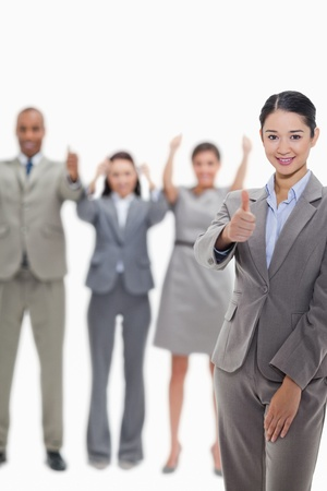 19's: Close-up of a businesswoman approving with hand gesture with enthusiastic co-workers raising their arms in the background