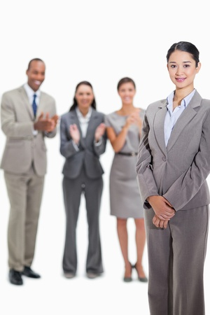 congratulating: Close-up of a businesswoman smiling with co-workers applauding and looking at her in the background