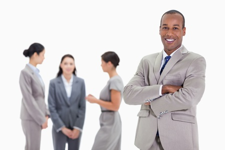 Close-up of a businessman smiling and crossing his arms with three female co-workers talking in the background Stock Photo - 13608597