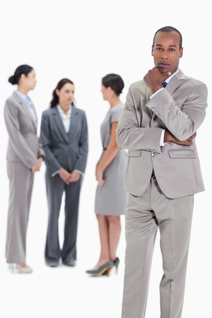 Serious businessman with a hand on his chin and three female co-workers talking seriously in the background Stock Photo - 13615044