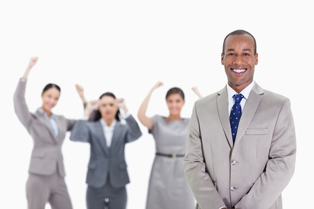 19's: Close-up of a happy businessman smiling with enthusiastic co-workers raising their arms in the background Stock Photo
