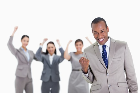 Close-up of a successful business team with man in foreground smiling and clenching his fist with three co-workers raising their arms photo