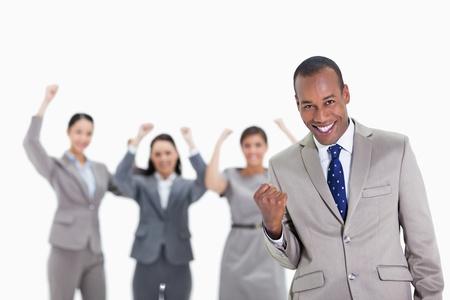 jonge ondernemers: Close-up van een succesvolle business team met de mens op de voorgrond glimlachen en balde zijn vuist met drie collega's de opvoeding van hun armen Stockfoto