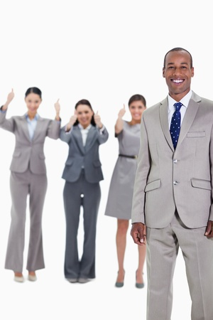 Happy businessman with three approving co-workers in background with thumbs up photo