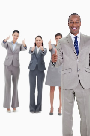 Business team smiling with thumbs up and with one businessman in foreground photo