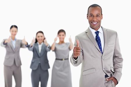 deacuerdo: Hombre de negocios feliz con una mano en el bolsillo y la aprobaci�n de los compa�eros de trabajo en el fondo con los pulgares para arriba Foto de archivo