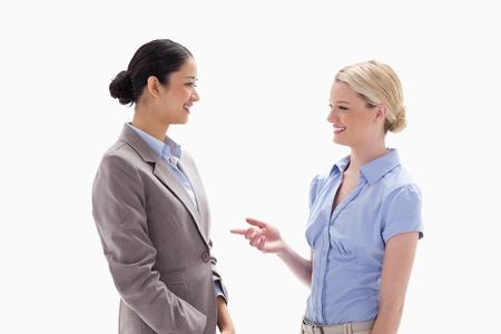dos personas conversando: Dos mujeres hablando alegremente contra el fondo blanco